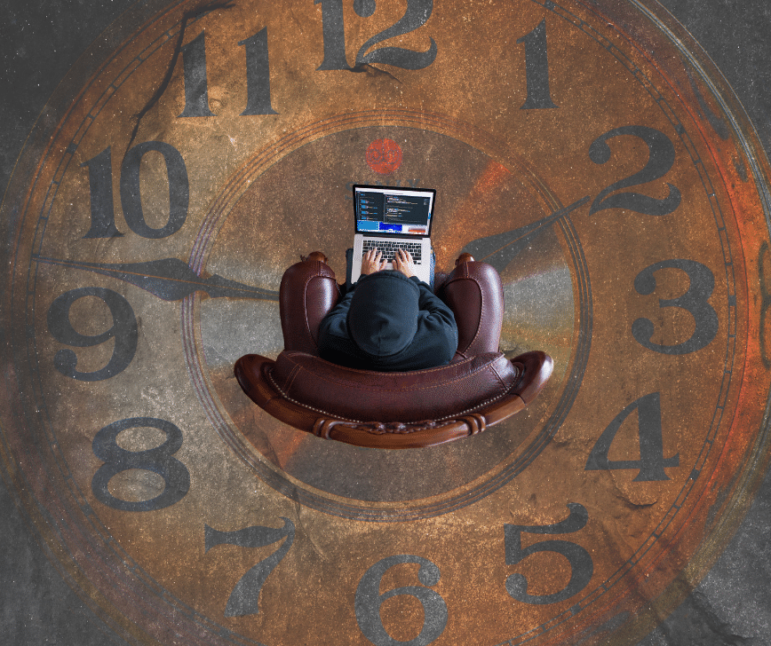 someone sitting in the middle of a large clock working a computer